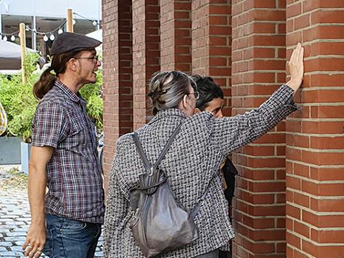 3 Personen betrachten die Fenster eines Backsteingebäudes